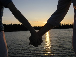 Holding hands silhouetted in front of sun set over water
