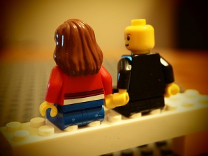 Lego couple sitting on block holding hands